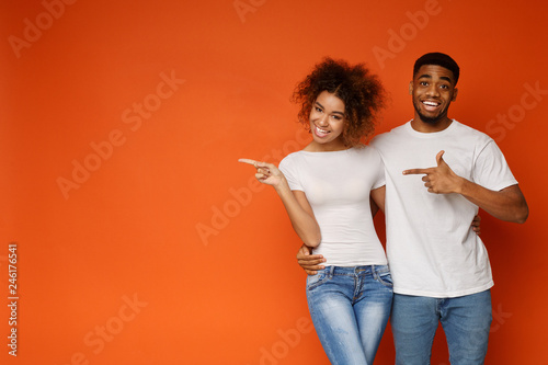 Fotografía  African-american man and woman point at empty space