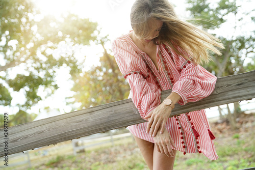Valokuva  Beautiful bohemian woman with windswept hair leaning on rustic fence