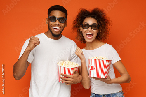 Photo  Laughing couple in 3d glasses holding buckets of popcorn
