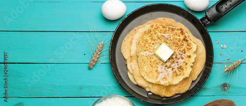 Hot delicious pancakes in frying pan on blue wooden table with flour and eggs, panoramic banner.