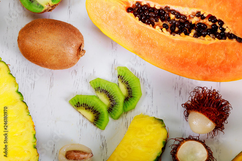 Exotic fruits on a the summer tropical composition papaya, kumquat, hranadylla, passion fruit.