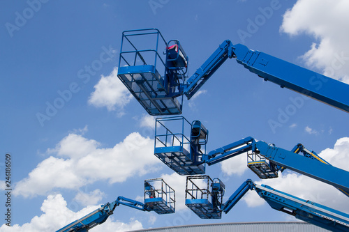 Photo  blue cherry picker over the metal factory roof against blue sky