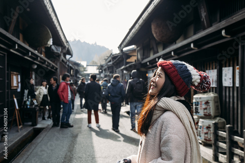 Asian cute girl standing with blur unidentify people in middle of Japanese old town with houses Edo style in Hida Takayama, Gifu, Japan.