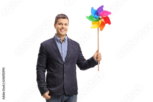 Handsome young man holding a colorful pinwheel and looking at the camera Canvas Print