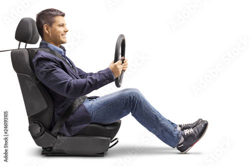 |Young man in a car seat with a fastened seat belt holding a streering wheel Tapéta, Fotótapéta