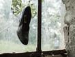 Schuh hängt in zerbrochener Fensterscheibe