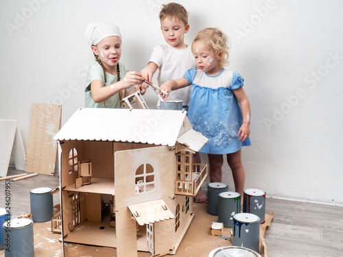 Photo  Children as adults: A boy and a girl paint a doll house white and get dirty with paint