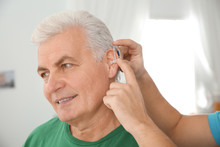 Young Man Putting Hearing Aid ...