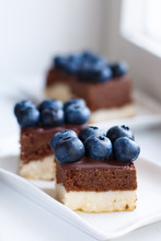 Three Slices Of Homemade Cheesecake With Chocolate Layer And Fresh Blueberry In Colors Of Estonian Flag (blue-black-white)