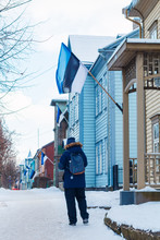 Young Man Walking Down The Street Of Karlova District Of Tartu, Estonia, Decorated With National Flags During Celebration Of 100 Years Of Estonian Independence 24 Feb. 2018