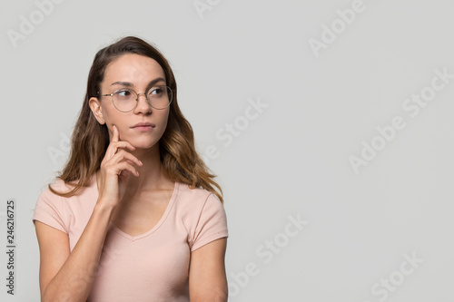 Valokuva  Thoughtful serious doubtful young woman with unsure face looking aside at copy free space for text feeling uncertain  thinking considering making decision isolated on white blank studio background