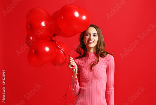 beautiful emotional girl in  pink dress with red ballons on red background Canvas Print