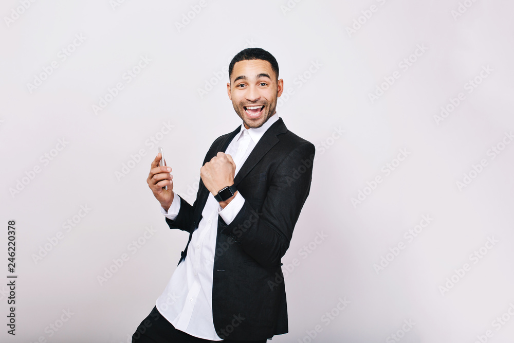Fototapeta Portrait young handsome man in white shirt, black jacket having fun, smiling to camera on white background. Success, expressing true positive emotions, good results, happiness, smiling