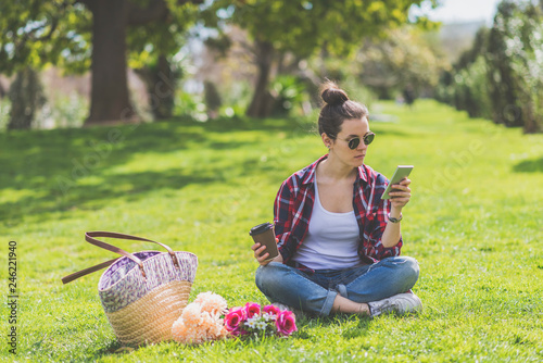 Front view of a young hipster woman wearing sunglasses, sitting on grass in a park while using a mobile phone - 246221940