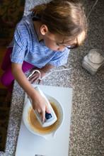 Girl Using Hand Mixer In Kitchen