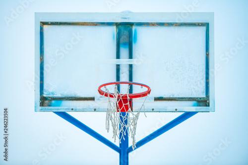 Fototapeta Frozen outdoor basketball hoop in winter snow