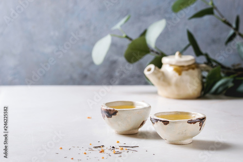 Hot green tea in two traditional chinese clay ceramic cup and teapot standing on white marble table Canvas Print