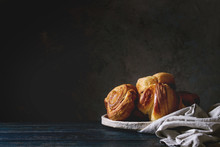 Variety Of Homemade Puff Pastry Buns Cinnamon Rolls And Croissant In Ceramic Plate On Wooden Table. Dark Still Life. Copy Space