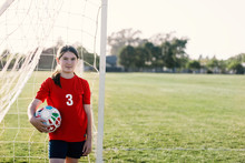 Portrait Of Girl Wearing Red Soccer Uniform Standing Against Goal Post During Sunny Day
