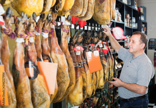 Poster Maroc Mature man selecting Spanish jamon leg