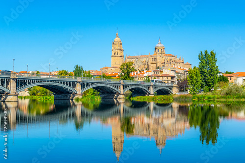 Cathedral at Salamanca reflected viewed behind bridge of enrique esteven on river Tormes, Spain