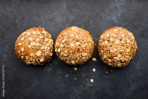 Wholegrain burger buns on dark background. Top view, space.