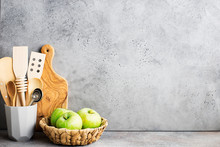 Kitchen Shelf. Gray Concrete Wall Kitchen Tools For Cooking, Wicker Basket With Green Apples, Cutting Board. Horizontal, Copy Space..