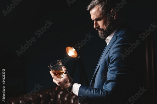 Poster de jardin Alcool Degustation, tasting. Man with beard holds glass of brandy. Tasting and degustation concept. Bearded businessman in elegant suit with glass of whiskey