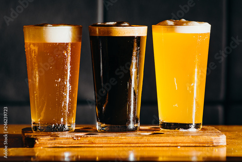 Tuinposter Bier / Cider Glasses of light and dark beer in a pub. Dark background.