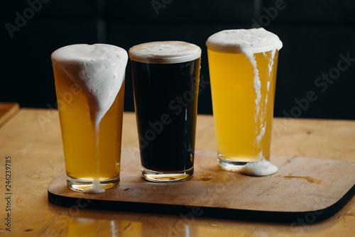 Tuinposter Bier / Cider Glasses of light and dark beer in a pub. Dark background.