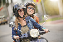 Happy Young Women Riding Scoot...