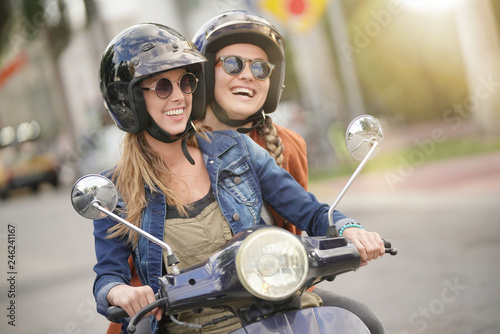 Fotografia Happy young women riding scooter together in city