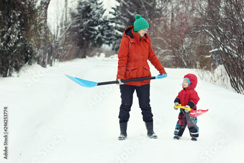 Fotografia, Obraz  Young mother and her toddler son stand with snow shovels on rural road