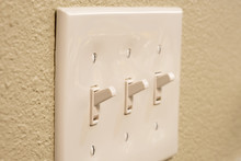Traditional North American Toggle White House Electric Light Switch In ON Position On Aged Old Wood Wall