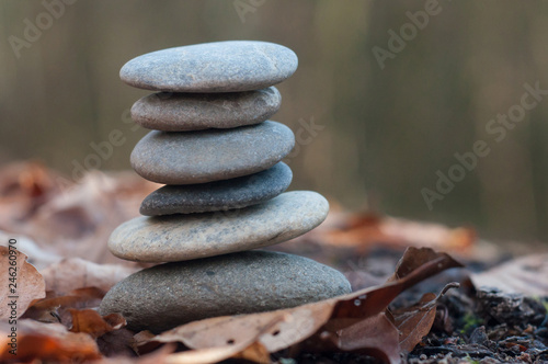 Photo Stands Stones in Sand Closeup of stone balance on autumnal leaves in the forest