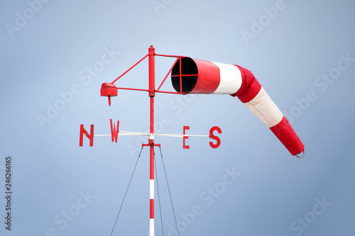 Red and white airport windsock with a clear blue sky background