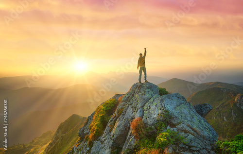 Fototapeta Silhouette of a champion on mountain top. Travel and adventure. Mountain hiking. Mountains during sunrise. Success and goal achievement. People success-image obraz