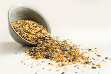 Bird Food From Mixed Seeds Like Sunflower, Corn, Millet And More, Are Falling Out Of A Bowl On A Light Background, Copy Space