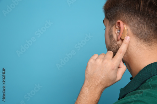 Valokuva  Young man adjusting hearing aid on color background