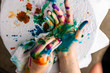 A child cleans up hands that are covered in red, pink, yellow, orange, red, blue, green, and purple ink. Concepts: art, education, play, watercolor, finger painting, mess, creativity, fun, enjoyment