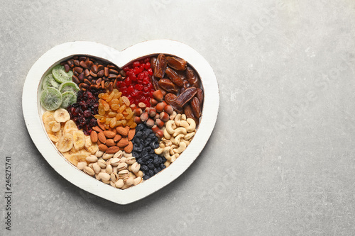 Heart shaped plate with different dried fruits and nuts on table. Space for text