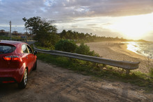 Red Rental Car Parked At Calm Beach At Sunset In Puerto Rico