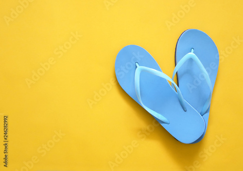 fc7190b8f251 Blue beach flip flop on yellow background with copy space. Summer holiday  concept.