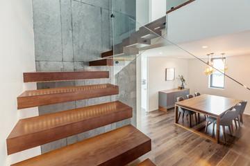 Nowoczesne wnętrze salonu ze schodami, szarymi kolorami, białymi ścianami