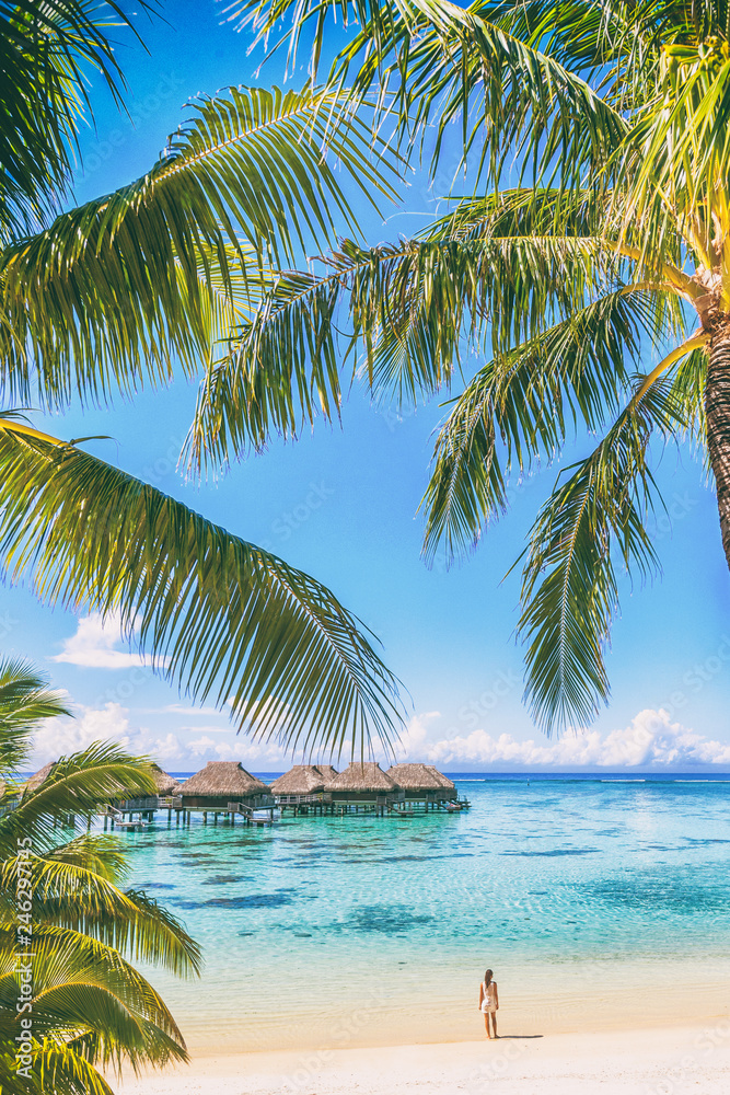 Fototapeta Tahiti luxuy travel resort overwater bungalow hotel in Bora Bora idyllic holiday woman in paradise vertical background with copy space on palm trees.