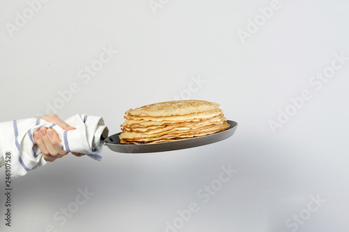 Fotografie, Obraz  Stack of russian pancake blini in pan woman holds in hands