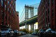 Manhattan bridge seen from a narrow alley enclosed by two brick buildings