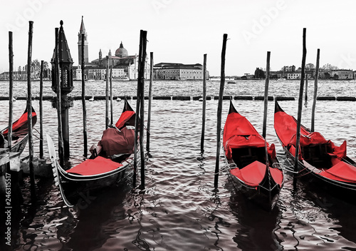 Blue old gondolas  docked at the pier the Piazza San Marco in Venice, Italy. Color in black and white