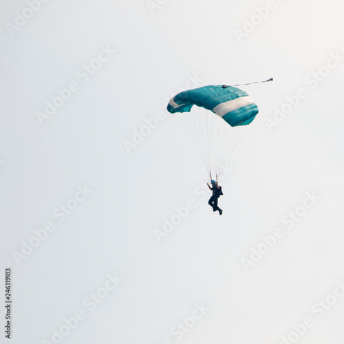Parachutist on blue sky preparing for landing