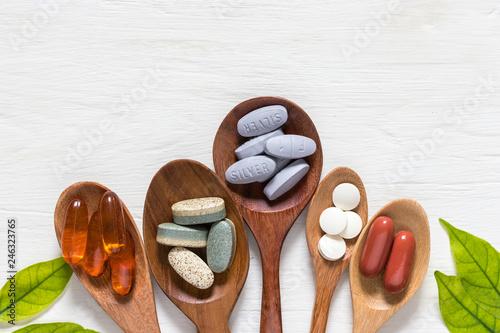 Obraz na płótnie Vitamin capsules in wooden spoons on white wooden background